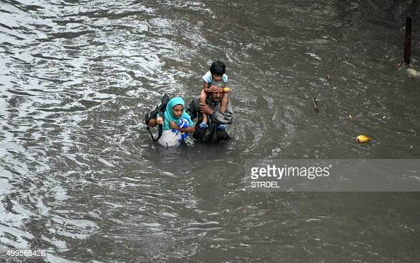 TOPSHOT An Indian family walk through floodwaters in Chennai on December 2 2015 India has deployed troops to Tamil Nadu and closed the main airport...