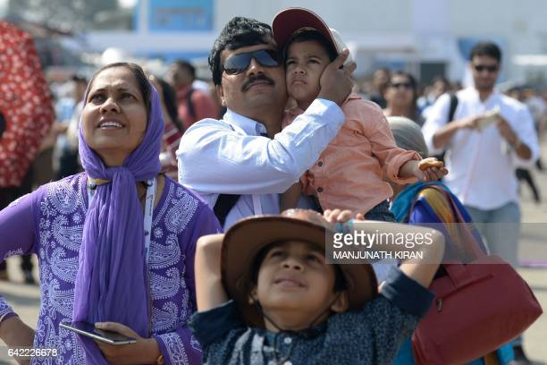 An Indian family watches an aerial display of aircraft on the fourth day of the 11th edition of 'Aero India' a biennial international aerospace and...
