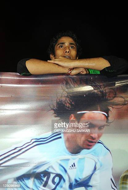 An Indian fan of Argentine footballer Lionel Messi leans on a poster of Messi as fans wait for Messi's arrival at the airport in Kolkata on August 31...