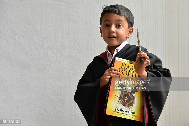 An Indian fan of Harry Potter dressed as the young wizard poses for a photograph after picking up a copy of JK Rowling's latest book 'Harry Potter...