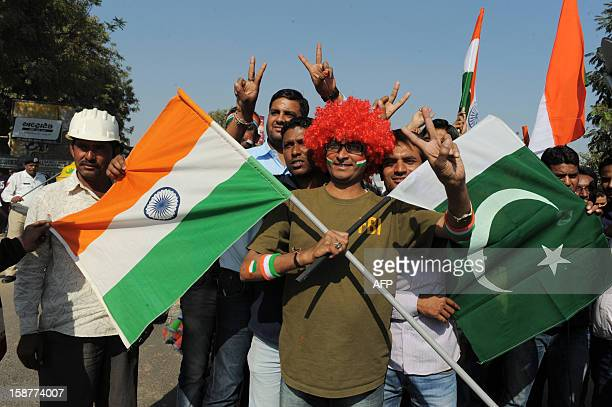 An Indian fan poses with flags of India and Pakistan outside the Sardar Patel Gujarat Stadium Motera near Ahmedabad on December 28 2012 Pakistan and...