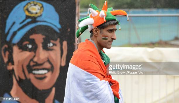 An Indian fan waits in the rain in front of a painting of India's MS Dhoni before the ICC Champions Trophy Final between England and India at...