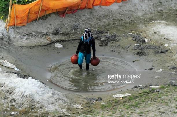 An Indian farmer collects water from a temporary pond to irrigate his cucumber farm near a river bed area of the River Ganges in Allahabad on April...