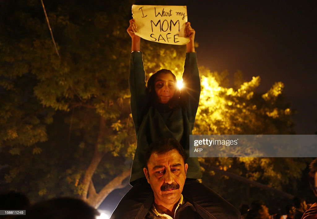 An Indian father carries his daughter holding a placard during a rally in New Delhi on December 30, 2012, following the cremation of a gangrape victim in the Indian capital. The victim of a gang-rape and murder which triggered an outpouring of grief and anger across India was cremated at a private ceremony, hours after her body was flown home from Singapore. A student of 23-year-old, the focus of nationwide protests since she was brutally attacked on a bus in New Delhi two weeks ago, was cremated away from the public glare at the request of her traumatised parents. AFP PHOTO/ ANDREW CABALLERO-REYNOLDS