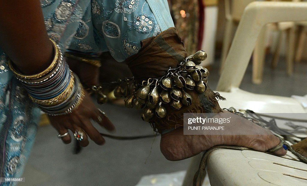 An Indian female artist ties on a musical anklet as she prepares for the 'Lavani' performance in Mumbai on April 8, 2013. Lavani is a genre of music, a combination of traditional song and dance which is particularly performed to the beat of the Dholki, a percussion instrument. The dance, noted for its powerful rhythm and erotic sentiment, is performed by female performers wearing nine-yard long saris. AFP PHOTO/ PUNIT PARANJPE