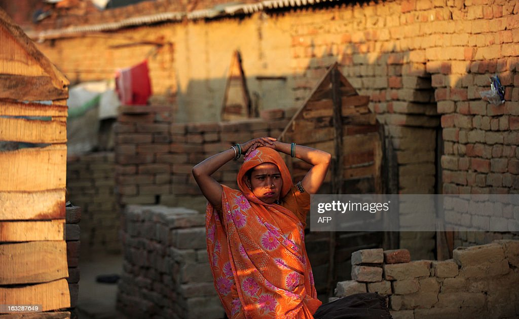 An Indian female labour stands outside her temporary shelter at a brick factory in Allahabad on March 7, 2013, on the eve of International Women's Day. Women have always faced higher unemployment rates than men, and the sluggish global economy in recent years has only made the situation worse, the International Labour Organisation said in December 2012. AFP PHOTO/ Sanjay KANOJIA