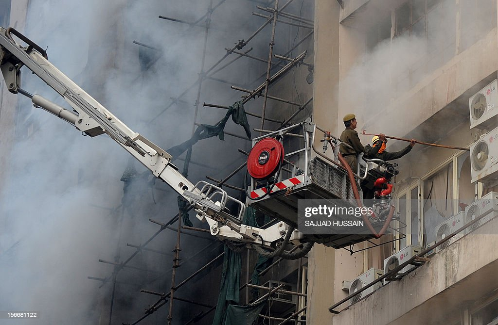 An Indian firefighter and a police officer investigate a fire that broke out in a fifteen story building in New Delhi early November 19, 2012. No casualities were reported in the fire.