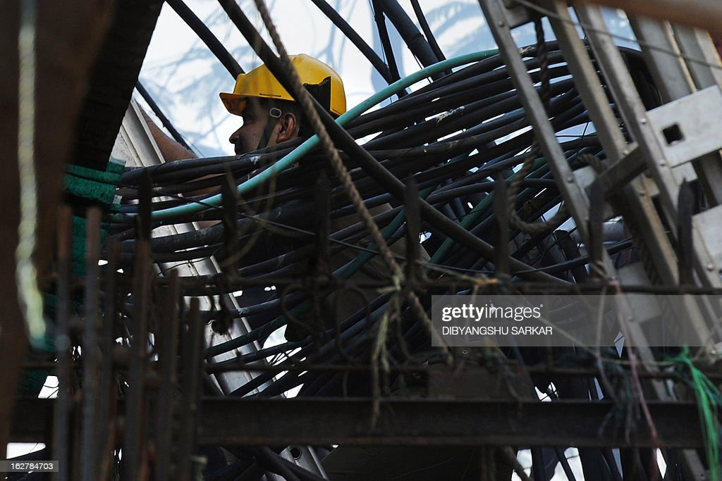 An Indian firefighter climbs past wiring as he attempts to control a blaze in the Surya Sen market building in Kolkata on February 27, 2013. A fire swept through a six-storey building housing an illegal market in the eastern Indian city of Kolkata, killing 13 people who were unable to escape the inferno, local officials said. AFP PHOTO/Dibyangshu SARKAR
