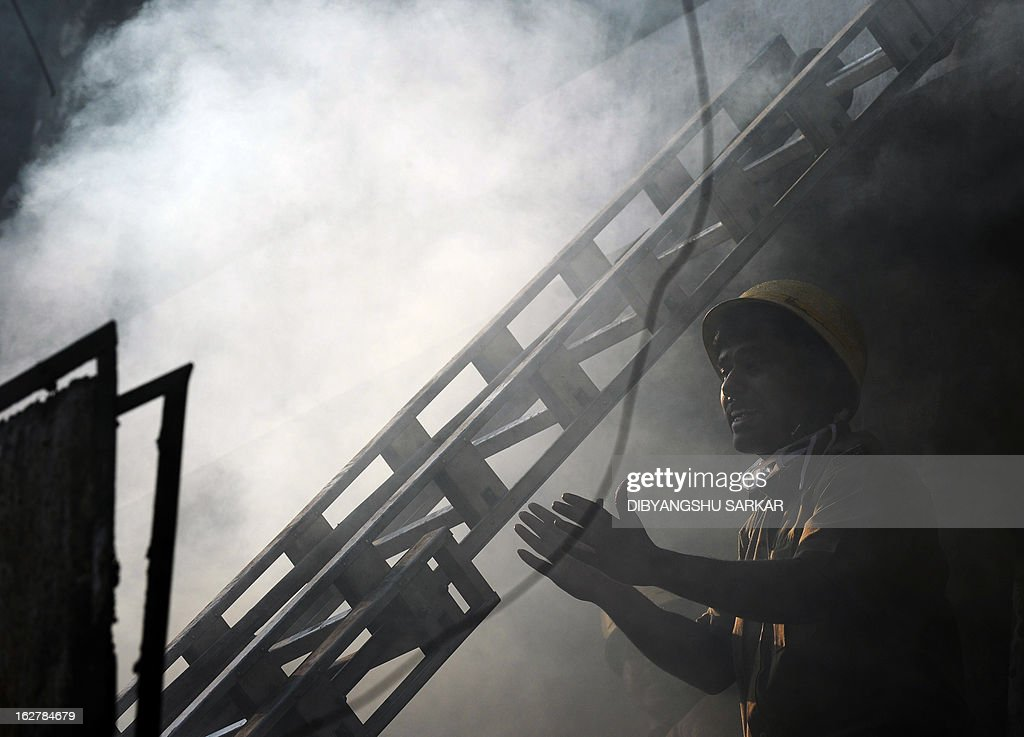 An Indian firefighter gestures as he attempts to control a blaze in the Surya Sen market building in Kolkata on February 27, 2013. A fire swept through a six-storey building housing an illegal market in the eastern Indian city of Kolkata, killing 13 people who were unable to escape the inferno, local officials said. AFP PHOTO/Dibyangshu SARKAR