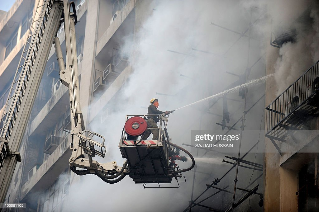 An Indian firefighter uses a hose in an attempt to control a fire that broke out in a fifteen story building in New Delhi early November 19, 2012. No casualities were reported in the fire. AFP PHOTO/SAJJAD HUSSAIN