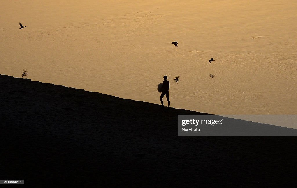 An indian fisher man returns after cathching fish on the partially dried banks of Ganges river, in Allahabad on May 6,2016..Much of India is reeling under weekslong heat wave and severe conditions that have decimated crops, killed livestock and left atleast 330 millions indians without enough water for their daily needs.