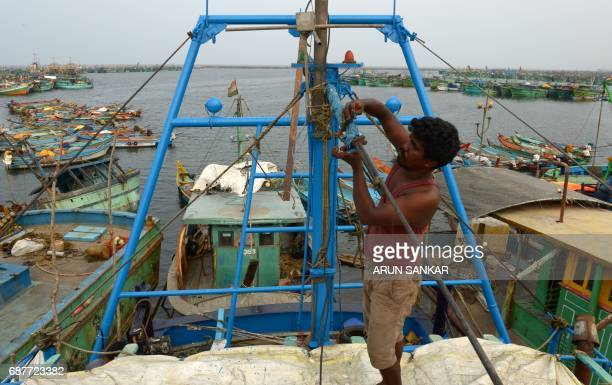 An Indian fisherman carries out maintainance on mechanised boats in Chennai on May 24 2017 Authorities in the southern Indian state of Tamil Nadu...