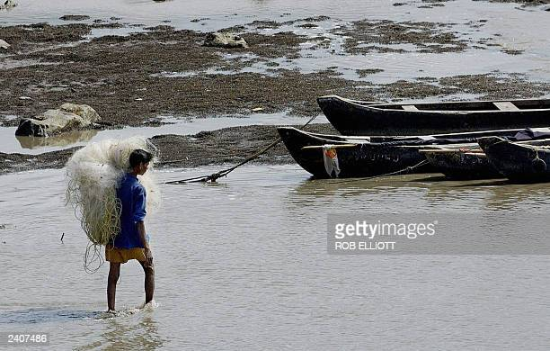 An Indian fisherman carrying his light nylon fishing net on his shoulders wades out to boats during low tide at Colaba fishing village Bombay 17...