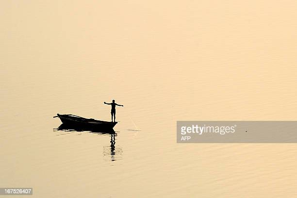 An Indian fisherman pulls in his net from a skiff over the Yamuna river in Allahabad on April 26 2013 Indian consumers feel the most guilty about...