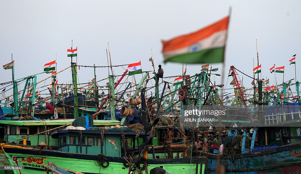 An Indian fisherman sits among fluttering national flags on mechanised boats in Chennai on May 29, 2016, as they prepare to set sail after a 45 day fishing ban on the east coast of India. Authorities in the southern Indian state of Tamil Nadu, had imposed a 45 day ban on fishing by mechanised vessels to protect marine life with only 'country boats' operating within five nautical miles of the coast exempted in the seas of The Bay of Bengal. / AFP / ARUN