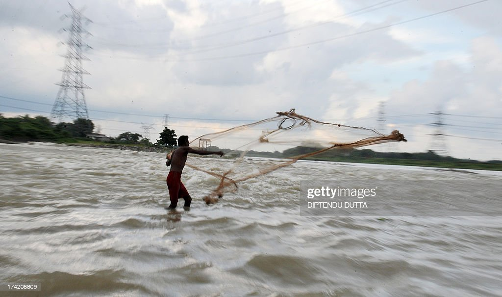 An Indian fisherman throws a net in the Mahananda river in Fulbari on the outskirts of Siliguri on July 21, 2013. Fish production is high during the monsoon season , which runs from June to September, accounts for about 80 percent of India's annual rainfall, vital for a farm economy which lacks adequate irrigation facilities. AFP PHOTO/ Diptendu DUTTA