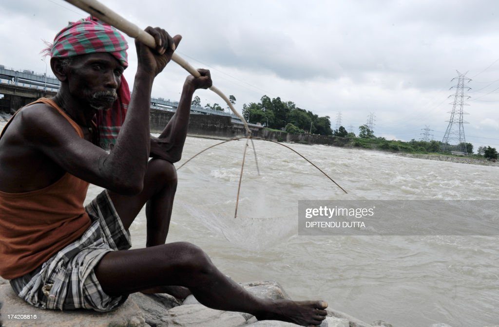 An Indian fisherman uses a handmade net to catch fish in the Mahananda river in Fulbari on the outskirts of Siliguri on July 21, 2013. Fish production is high during the monsoon season , which runs from June to September, accounts for about 80 percent of India's annual rainfall, vital for a farm economy which lacks adequate irrigation facilities. AFP PHOTO/ Diptendu DUTTA