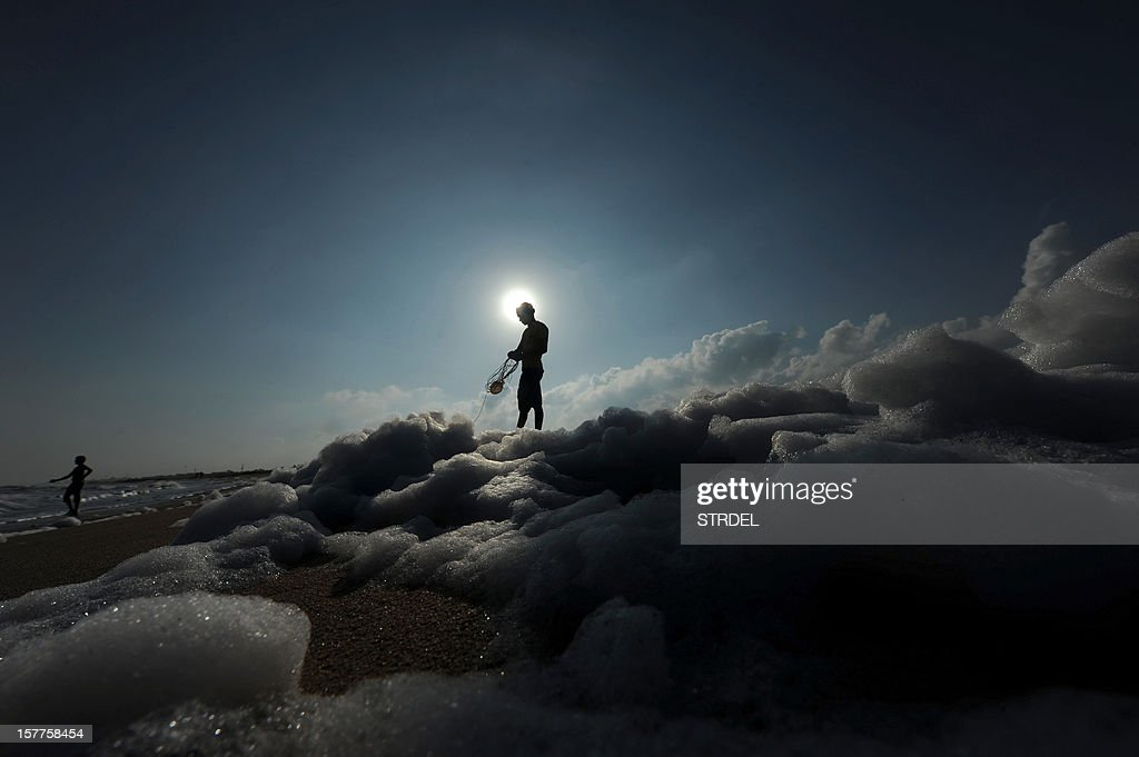 An Indian fishermen pulls in his fishing net as foamy discharge, caused by pollutants, mix with surf at a beach in Chennai on December 6, 2012. High levels of sewage and industrial waste was claimed to be the cause of the foam, according to officials.