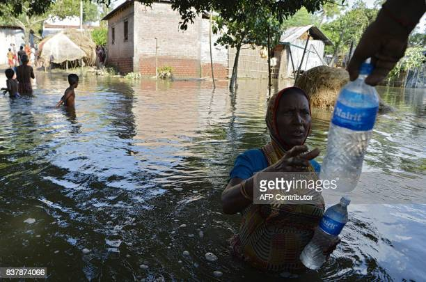 An Indian flood effected villager collects drinking water at Alal village in Malda district in the Indian state of West Bengal on August 23 2017 More...