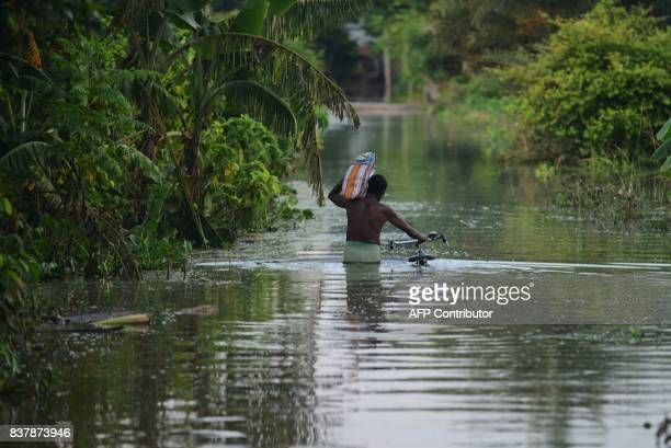 An Indian flood effected villagers wade through flood waters in Alal village in Malda in the Indian state of West Bengal on August 23 2017 More than...