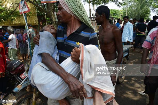 An Indian flood victim is carried to a temporary medical camp for treatment in the Amta area of Howrah district around 55km west of Kolkata on July...