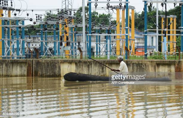 An Indian flood victim on a boat makes his way past an electricity plant through flood waters in the Amta area of Howrah district around 55km west of...