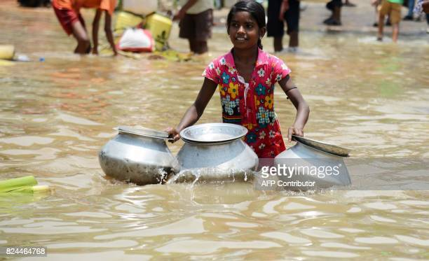 An Indian flood victim with containers wades through the flood water to collect drinking water in the Amta area of Howrah district around 55km west...