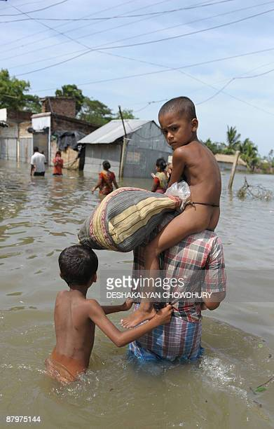 An Indian floodaffected villager carries his child to safety in the flooded village of Sandeshkhali some 100 kms south east of Kolkata on May 26 2009...