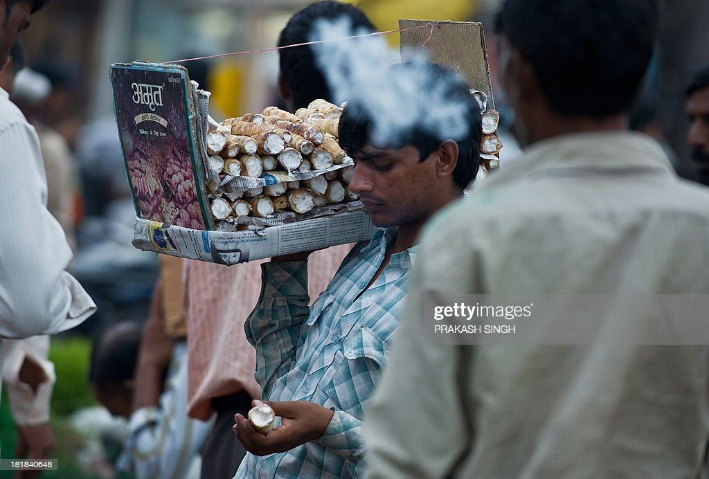 An Indian food vender sells cream rolls at a wholesale flower market in New Delhi on September 26, 2013. India's inflation rose unexpectedly in August to a six-month-high, data shows, adding to challenges confronting the new central bank chief, who is already grappling with a slowing economy and a weak currency. AFP PHOTO/ Prakash SINGH