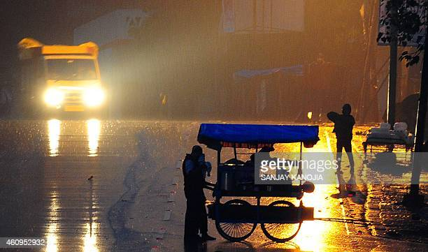 An Indian food vendor pushes his cart during a downpour of rain along a street in Allahabad on January 1 on the occasion of New Year AFP PHOTO...