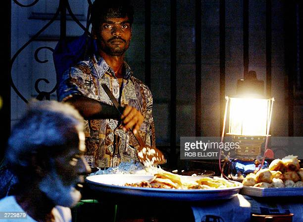 An Indian food vendor using a lantern to see cooks onions as he prepares for night trading in the streets of Bombay 14 November 2003 Many Indian...
