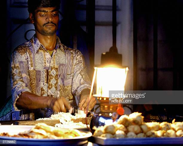 An Indian food vendor using a lantern to see cuts up onions as he prepares for night trading in the streets of Bombay14 November 2003 Many Indian...