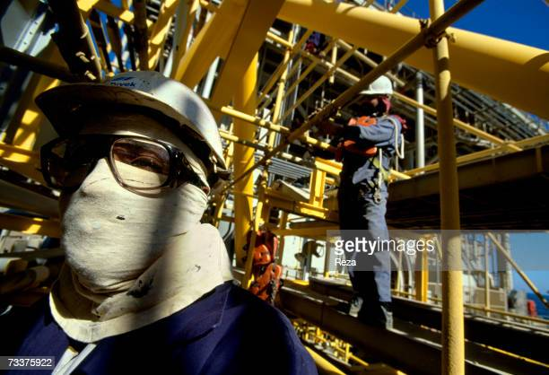 An Indian foreign 'guest worker' stands in the technical zone of the gas and petrol separation at the Aramco offshore oil rig 'Marjan 2' in the...