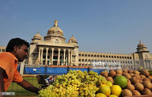 An Indian fruit vendor pushes his cart past the Vidhana Soudha building in Bangalore on February 26 2010 Vidhana Soudha houses the Legislaive...