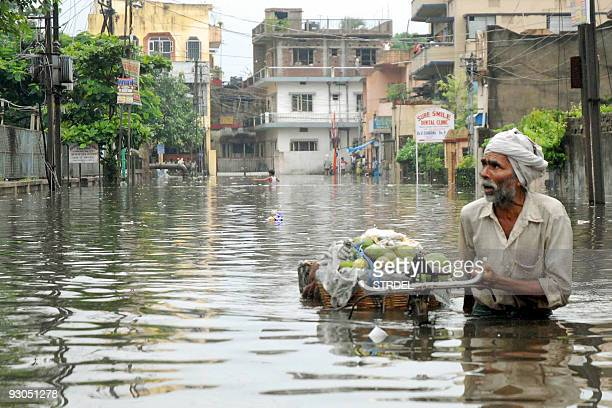 An Indian fruit vendor pushes his laden bicycle along a flooded street in Patna on July 15 2008 Areas of the Indian state of Bihar of which Patna is...