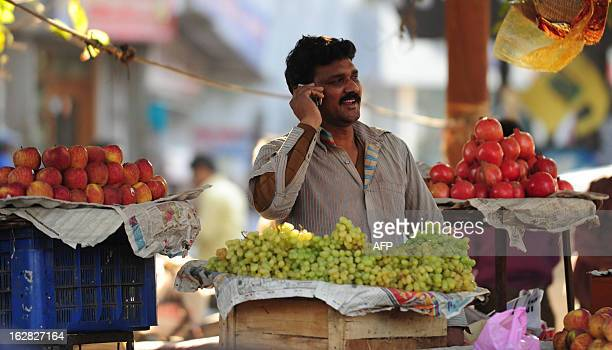 An Indian fruit vendor speaks on his mobile phone at a market in Allahabad on February 28 2013 India's government increased spending by 16 percent as...