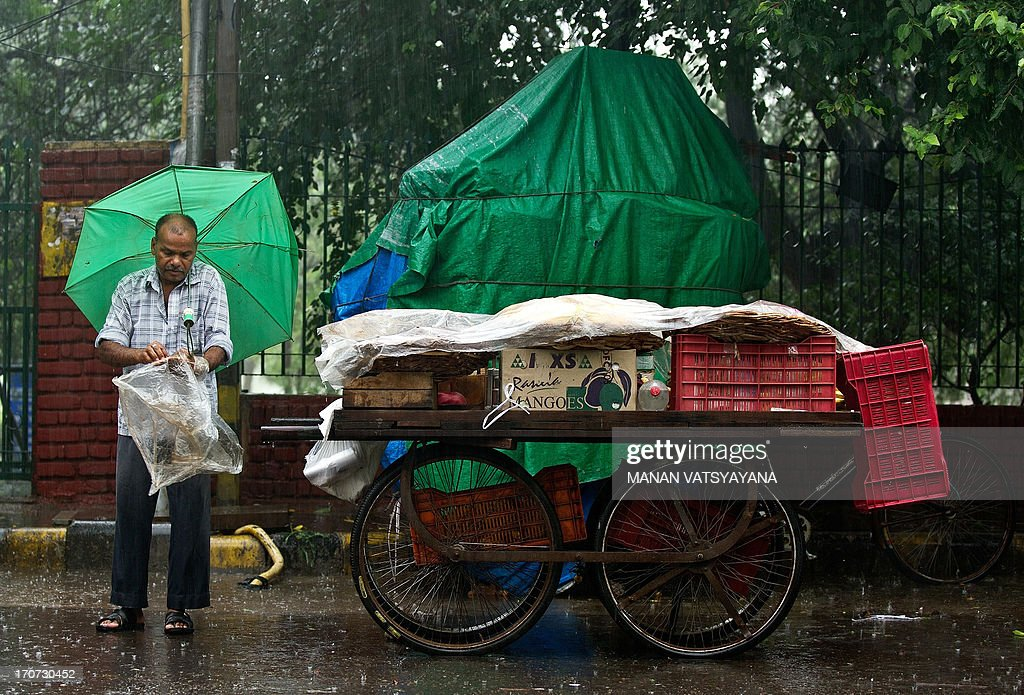 An Indian fruit-seller covers his cart with a plastic sheet during a heavy downpour in New Delhi on June 17, 2013. According the India Meteorological Department (IMD) , Indias monsoon, which accounts for more than 70 percent of the annual rainfall, may be the highest in two years, potentially boosting harvests of everything from rice to corn, sugar cane and cotton. The IMD reported that rainfall will be 98 percent of the 50-year average of 89 centimetres (35 inches) in the four months through September.