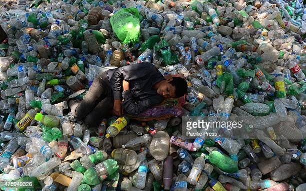 An Indian garbage collector sleeps on the waste plastic bottles on World Environment Day The world Environment Day is celebrated on June 5 every year...