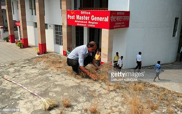 An Indian General Post Office employee cleans weeds from a building as part of the countrywide 'Clean India Campaign' in Allahabad on October 2 2014...