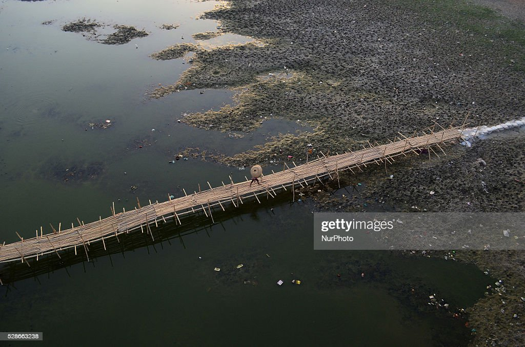 An Indian girl carring basket on her head,crosses the partially dried Ganges River on a temporary bamboo bridge ,during a hot day in Allahabad on May 6,2016...Much of India is reeling under weekslong heat wave and severe conditions that have decimated crops, killed livestock and left atleast 330 millions indians without enough water for their daily needs.