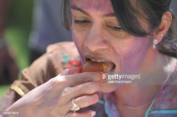 An Indian girl eats a Gulab Jamun a popular Indian dessert during a break at an ecofriendly Holi during 'Rangotsav 2012' at the Chokhidhani in...