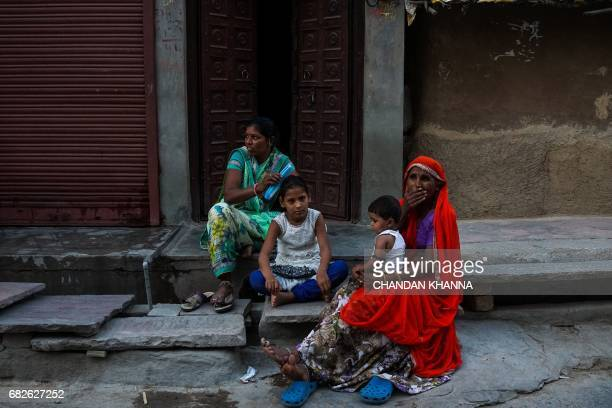 An Indian girl gets her hair done by her mother as they sit outside their house in Kekri some 78 kms south of Ajmer on May 13 in the northern state...