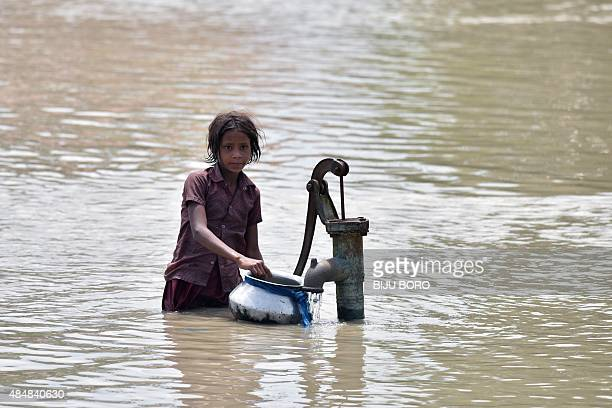 An Indian girl gets water from a partially submerged well in floodaffected Pavakati village some 70 km from Guwahati in Assam state on August 22 2015...