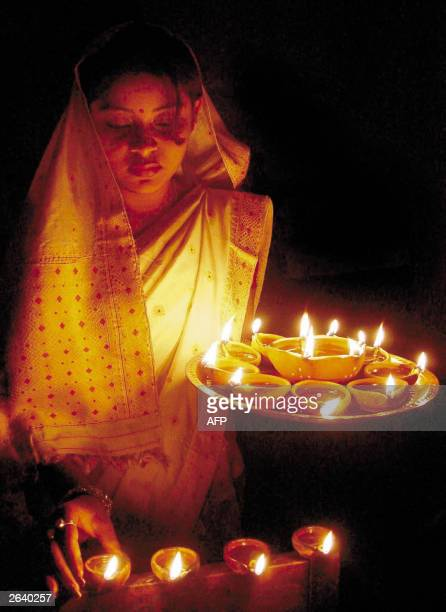 An Indian girl lights candles on the eve of the Diwali festival in Guwahati 24 october 2003 Diwali 'The Festival of light' is the largest Hindu...