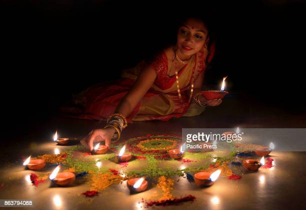 An Indian girl lights earthen lamps on the eve of Diwali in Kolkata in India