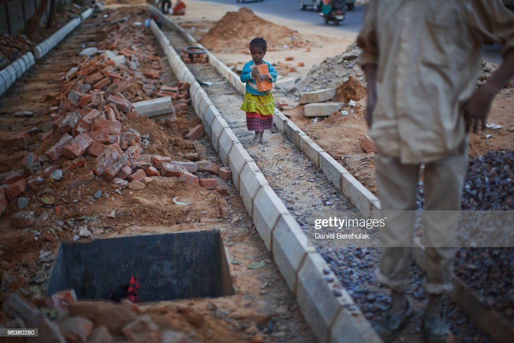 An Indian girl plays at a construction project in front of the Jawaharlal Nehru Stadium on February 03, 2010 in New Delhi, India. The children accompany their parents to the work site, where if they are prepared to work, they will receive money for bread an milk and be provided with dinner by the contractor. The Commonwealth Games are due to be held in the Indian capital from October 3-14, 2010, but concerns remain over construction of its sporting and transport infrastructure. The sheer scale of the project has drawn an enormous population of migrant workers from all over India. This week the High Court of Delhi has sought a response from the Government over the alleged failure to provide all the benefits of labour laws to workers involved in construction work for the coming Commonwealth Games. Workers are being paid below the minimum wage in order to complete these projects whilst also being forced to live and work under sub standard conditions.