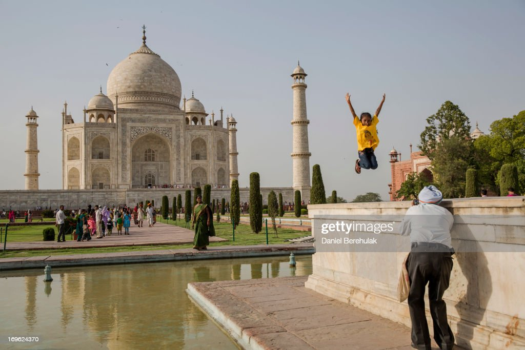 An Indian girl poses for a photograph as tourists visit the Taj Mahal on May 29, 2013 in Agra, India. Completed in 1643, the mausoleum was built by the Mughal emperor Shah Jahan in memory of his third wife, Mumtaz Mahal, who is buried there alongside Jahan.