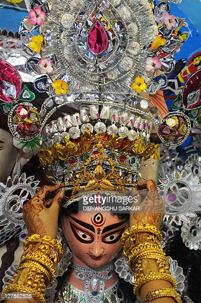 An Indian girl puts traditional gold jewellery on the clay idol of Goddess Durga in Kolkata on October 2 2011 The fiveday Durga Puja festival that...