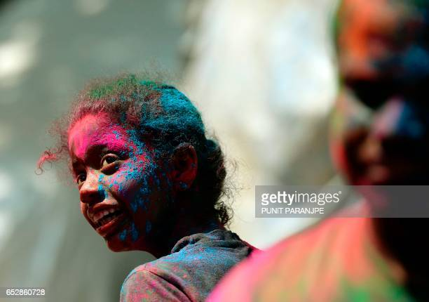 An Indian girl takes part in Holi celebrations in Mumbai on March 13 2017 Holi the festival of colours is a riotous celebration of the coming of...