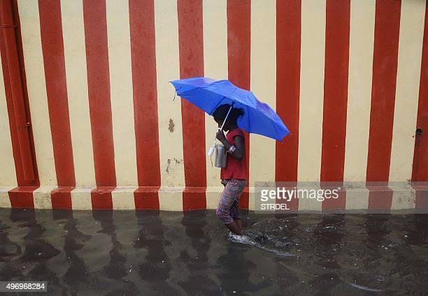 An Indian girl walks under an umbrella along a waterlogged street following heavy rain in Chennai on November 13 2015 AFP PHOTO / STR / AFP / STRDEL